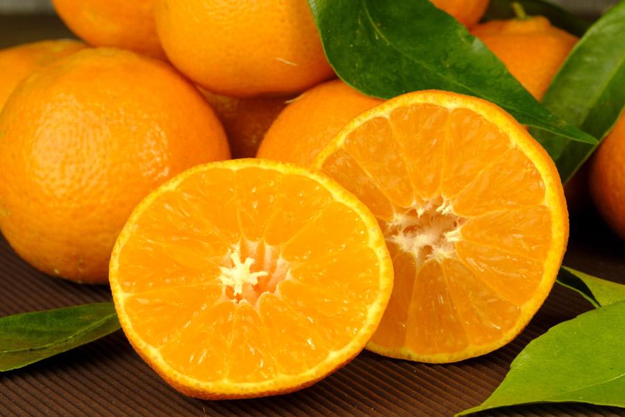 テーブルに乗っている、葉がついたオレンジ。オレンジの断面図。