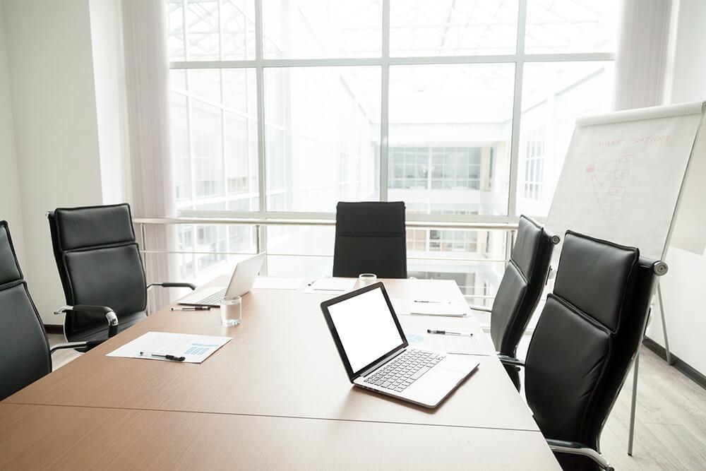 オフィスの会議室。黒い椅子にホワイトボード、テーブル。